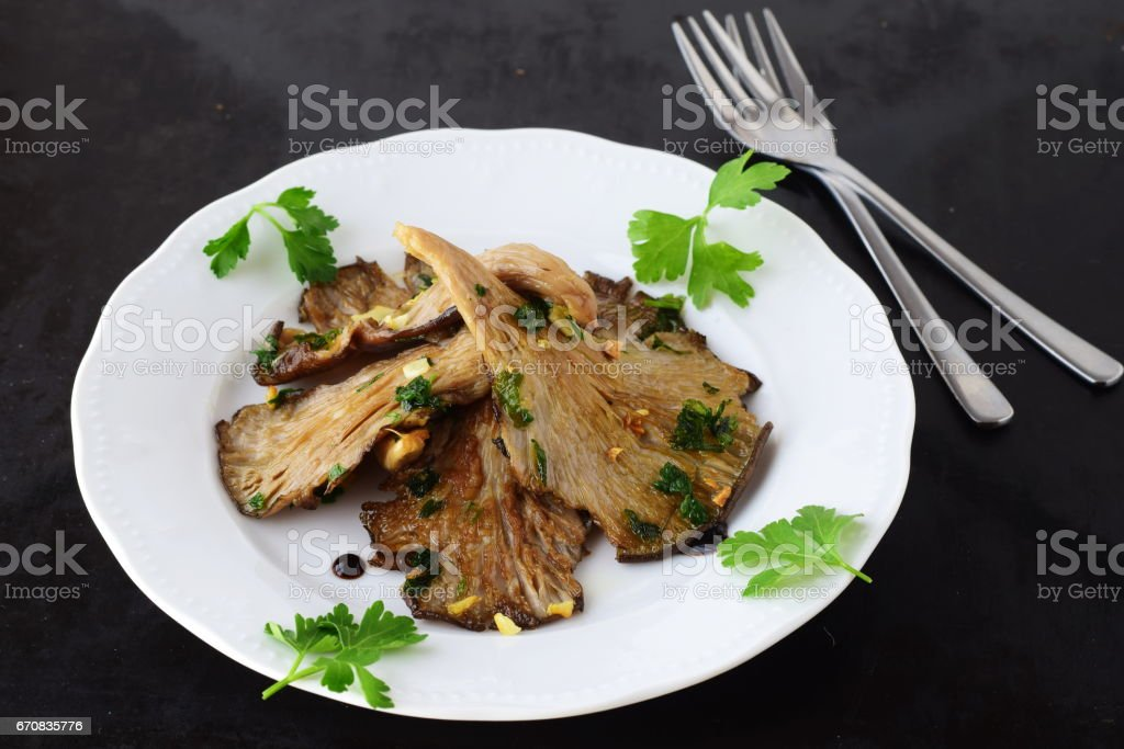 Fried Oyster mushrooms with garlic, parsley and balsamic glaze in a white plate on a black abstract background. Healthy concept stock photo