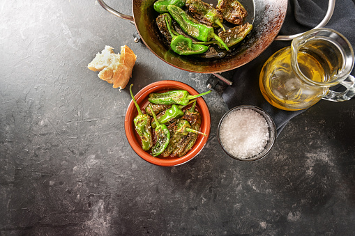 Fried peppers de padron or green pimientos in a pan and a traditional Spanish tapa bowl, salt, olive oil and bread on a dark gray background, copy space, high angle view from above