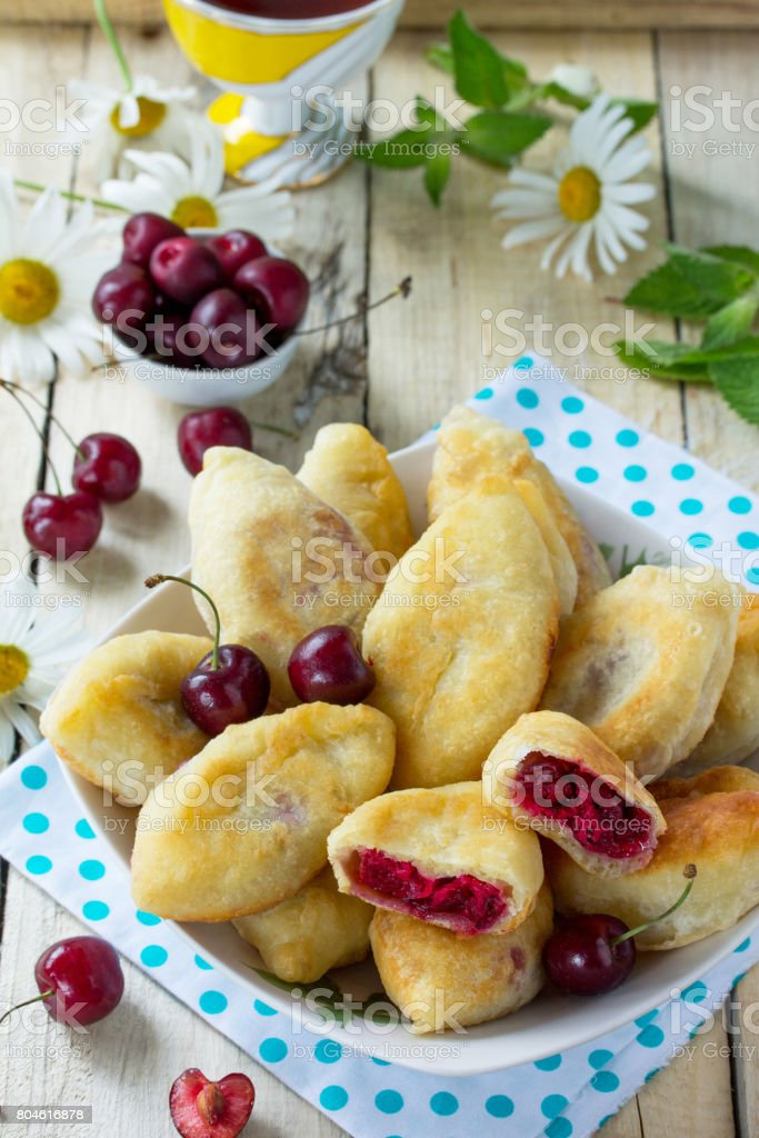 Fried pies. Pies sweet with cherries on the kitchen table in a rustic style. stock photo