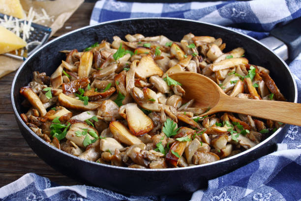 fried porcini with parsley in skillet - fungus stock pictures, royalty-free photos & images