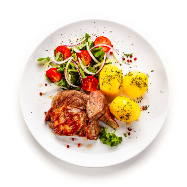 Fried pork and vegetables on white background stock photo
