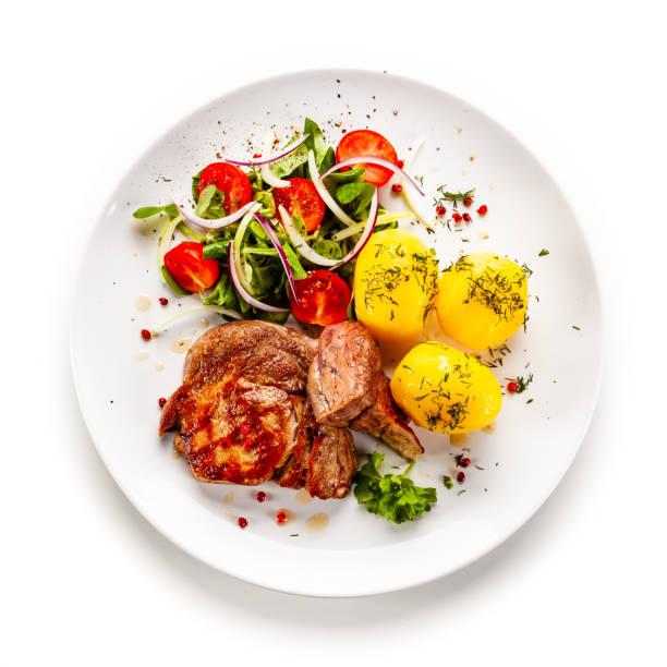 Gebratenes Schweinefleisch und Gemüse auf weißem Hintergrund – Foto