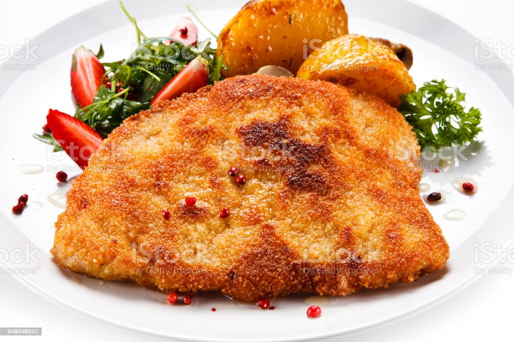 Fried pork chop and vegetables on white background stock photo