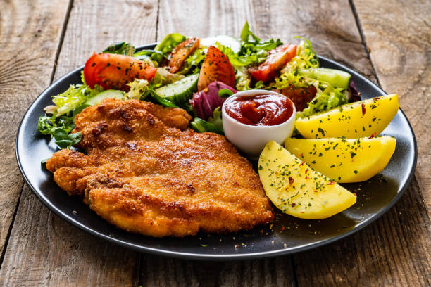 Fried pork chop, boiled potatoes and vegetable salad on wooden backgound stock photo