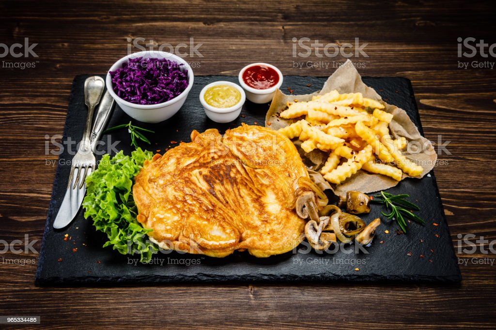 Fried pork chop, French fries and vegetables royalty-free stock photo
