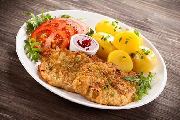 fried pork chops, boiled potatoes and vegetables - kürbisschnitzel stock-fotos und bilder