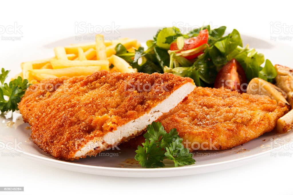 Fried pork chops, French fries and vegetables stock photo