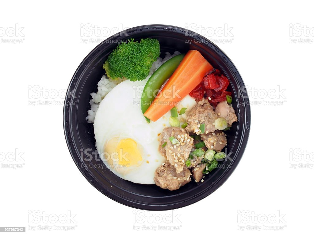 fried pork with korean sauce and rice, fried egg with steamed vegetables in black plastic tray isolated on white background stock photo