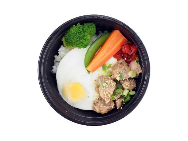 gebratenes schweinefleisch mit koreanische sauce und reis, spiegelei mit gedünstetem gemüse in schwarzen plastikschale isoliert auf weißem hintergrund - eierverpackung stock-fotos und bilder