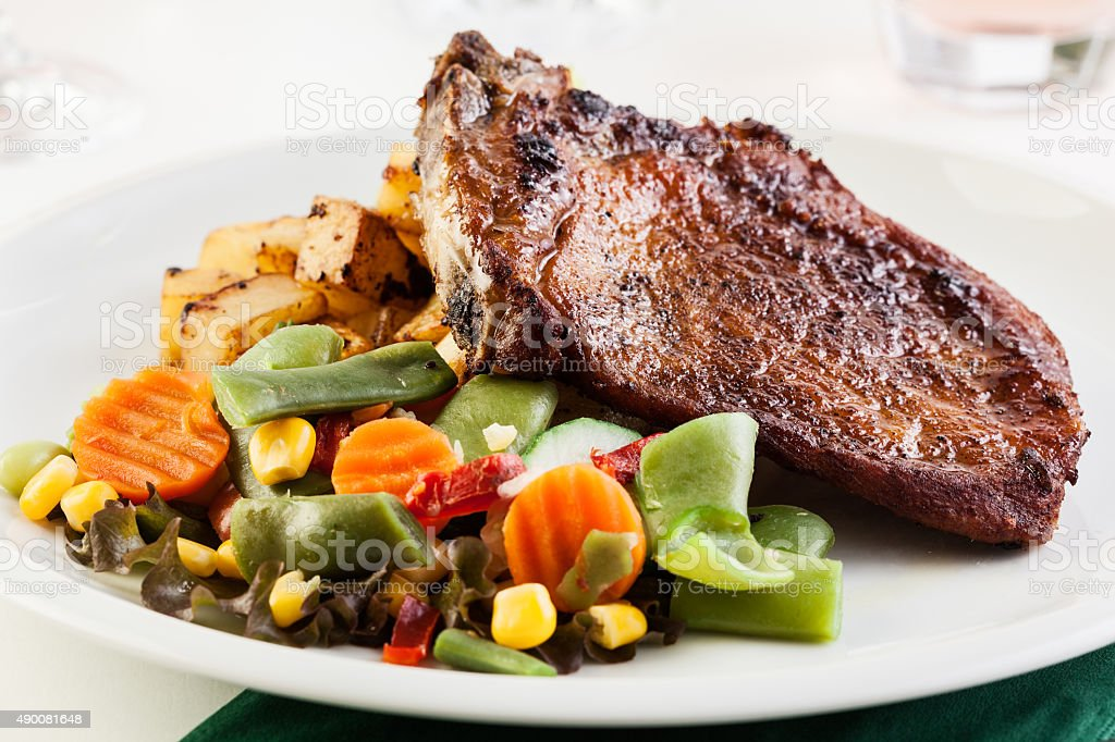 Fried pork with potatoes and vegetables salad stock photo