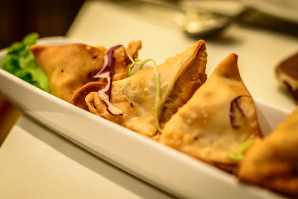 fried potato samosa appetiser in indian restaurant - appetiser stock photos and pictures