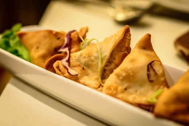 Fried potato samosa appetiser in Indian restaurant stock photo