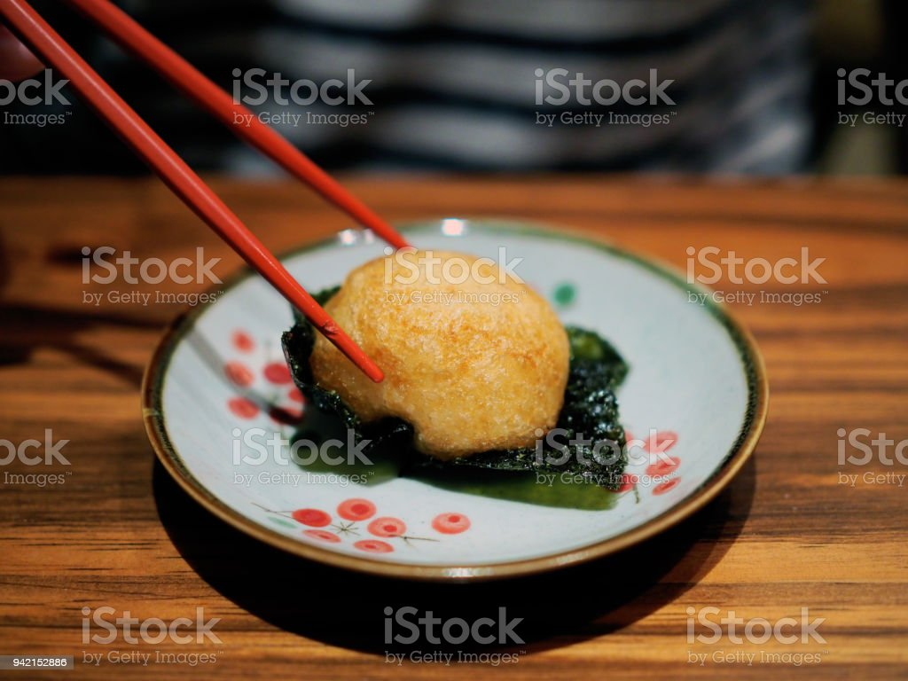 Fried potato stuffed with sea eel over seaweed served with lemon sliced. stock photo