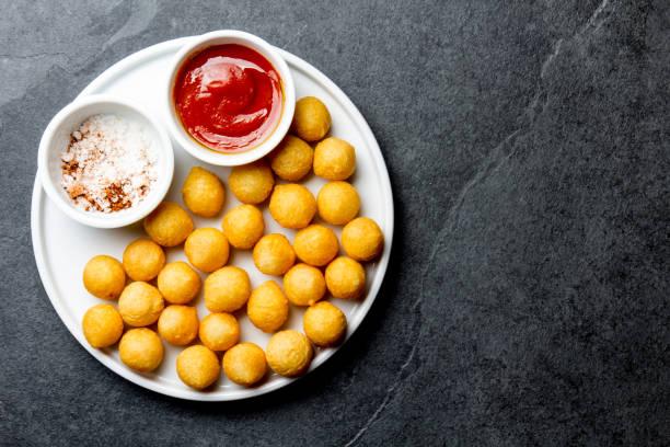 Bola de batatas fritas, crocettes na chapa branca com molho de tomate, fundo de ardósia, vista superior - foto de acervo