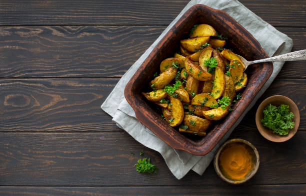 Fried potatoes in a clay cooking tray stock photo