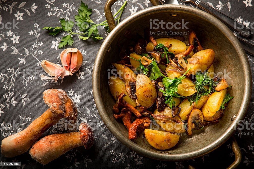 Fried potatoes with mushrooms, onions  in a frying pan stock photo