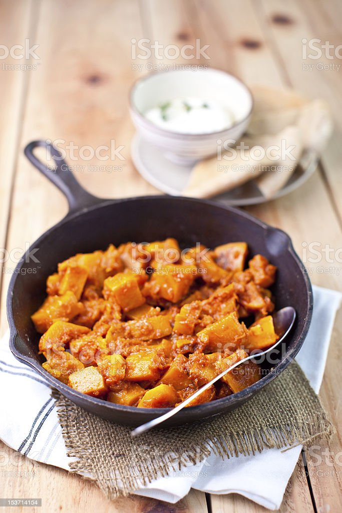 Fried pumpkin with  tomato sauce in cast-iron pan royalty-free stock photo