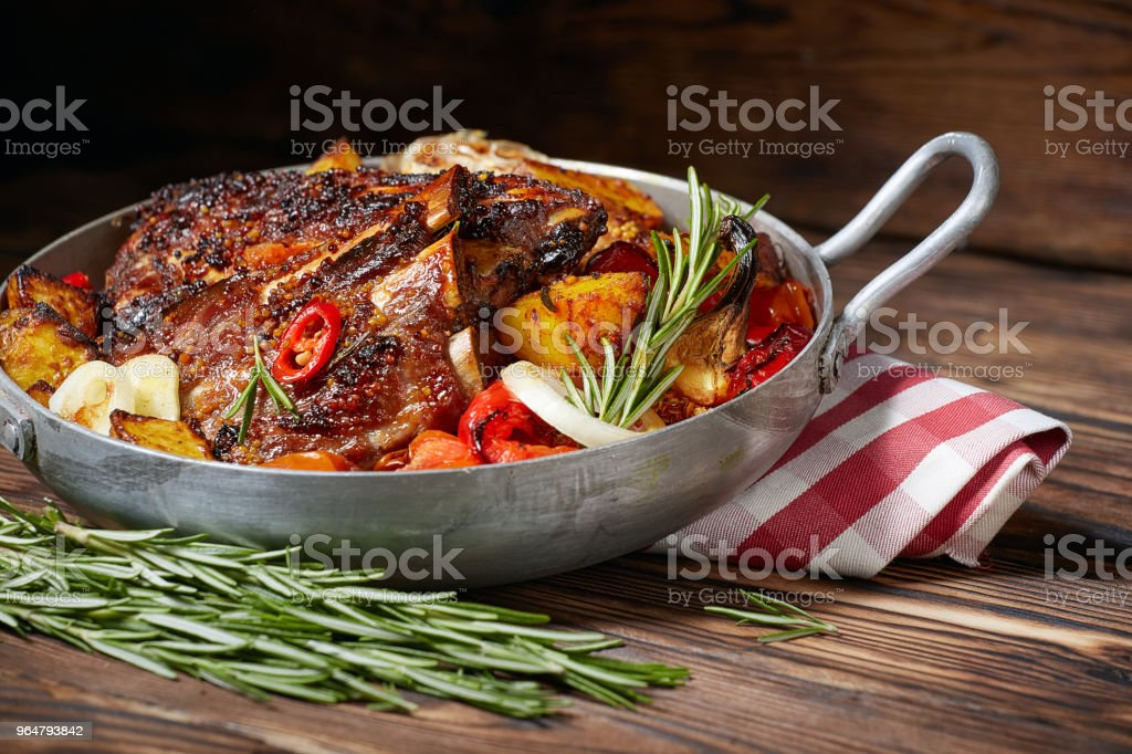 Fried ribs in a pan with rosemary, potatoes rustic, onion, sauce . Dark background. royalty-free stock photo