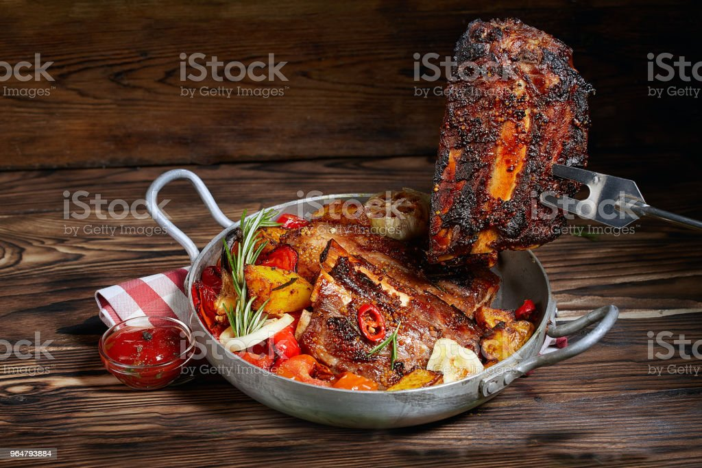 Fried ribs in a pan with rosemary, potatoes rustic, onion, sauce . Ribs are strung on a meat fork. Dark background. Place for text, copyspace royalty-free stock photo