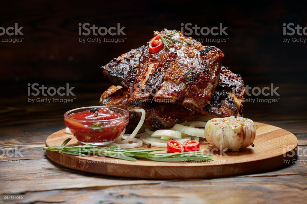 Fried ribs with rosemary, onion, sauce on a wooden round Board. Dark background. Place for text, copyspace royalty-free stock photo