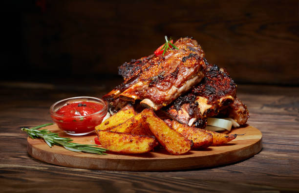 Fried ribs with rosemary, potatoes rustic, onion, sauce on wooden round Board. Dark background. Place for text, copyspace Fried ribs with rosemary, potatoes rustic, onion, sauce on wooden round Board. Dark background. Place for text, copyspace pork stock pictures, royalty-free photos & images