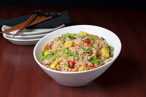 Fried Rice Fresh hot fried rice on a dark background with chopsticks and plates fried rice stock pictures, royalty-free photos & images