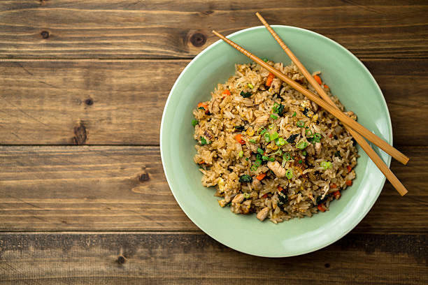 Fried Rice Top View on a Wooden Background Bowl of fried rice viewed from above with some chopsticks on the side. This asian inspired recipe uses lots of fresh ingredients like basil, carrots, onions and there's also fried eggs and chicken. fried rice stock pictures, royalty-free photos & images