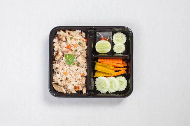 Gebratener Reis mit gebratenem Thunfisch in schwarze Plastikbox gesteckt, auf eine weiße Tischdecke, Lebensmittelkiste, thailändisches Essen gelegt. – Foto