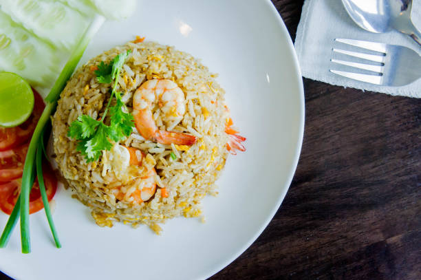 Fried rice with shrimp in a white dish on wood table in thai food style Fried rice with shrimp in a white dish on wood table in thai food style fried rice stock pictures, royalty-free photos & images
