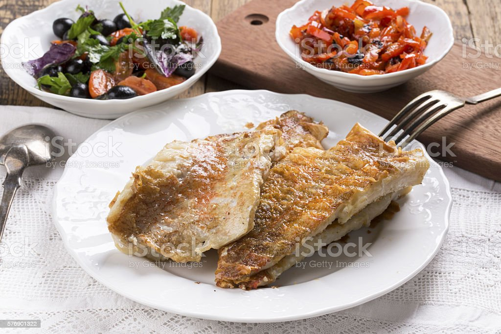 Fried rose fish fillet on a white plate. stock photo