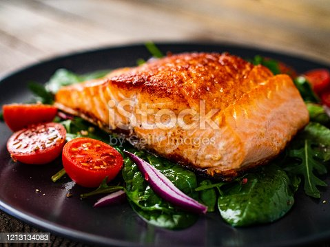 Barbecued salmon and vegetables on wooden background