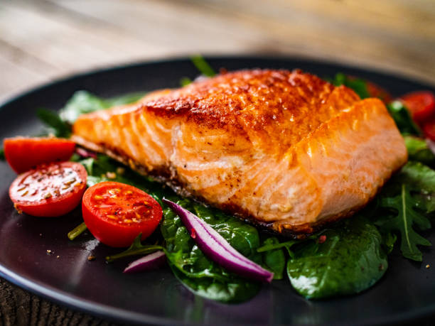 Fried salmon and vegetables on wooden background stock photo