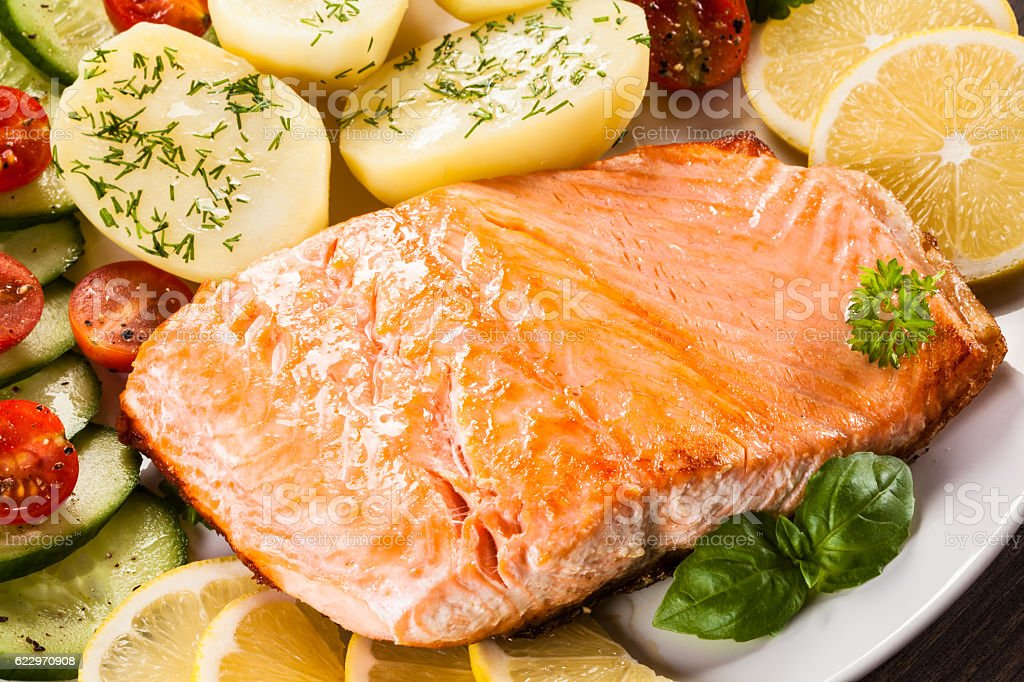 Fried salmon, boiled potatoes and vegetable salad stock photo