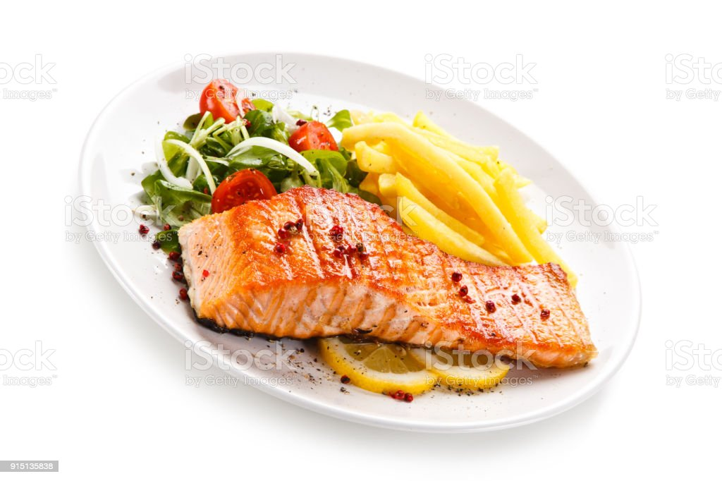 Fried salmon, French fries and vegetables stock photo