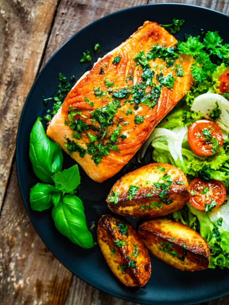 Fried salmon, fried potatoes and vegetables on wooden background stock photo