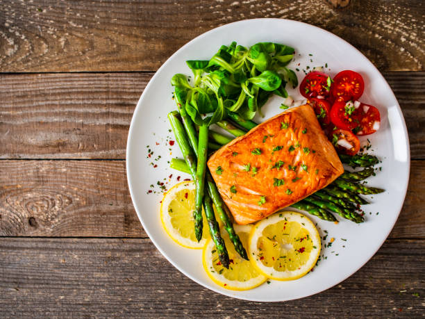 Fried salmon steak and asparagus on wooden table stock photo