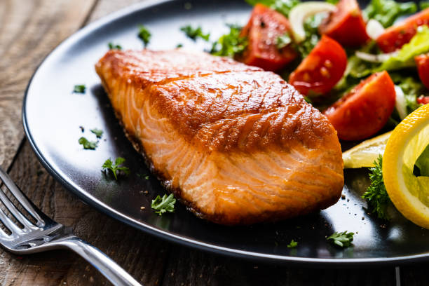 Fried salmon steak and vegetables served on black plate on wooden background stock photo