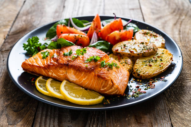 Fried salmon steak, fried potatoes and vegetables on wooden background stock photo