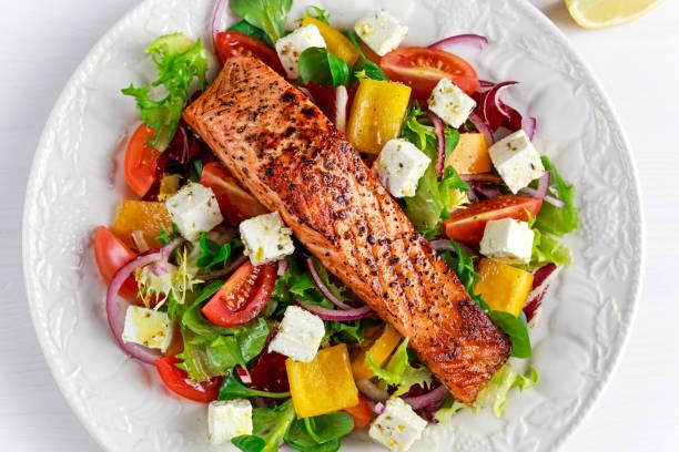 gebratener lachs-steak mit frischem gemüse salat, feta-käse. gesunde ernährung konzept. - gemüse zu fisch stock-fotos und bilder