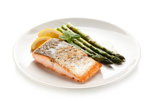 Fried salmon with asparagus on white background