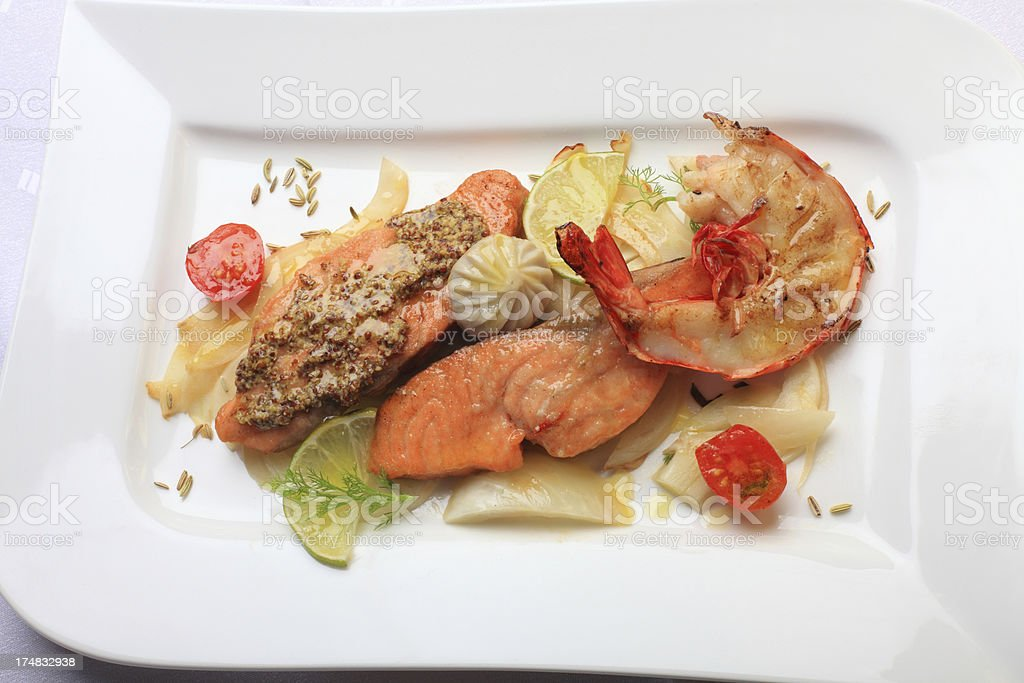 fried salmon with mustard, prawn, lime, fennel and artichoke bottom stock photo