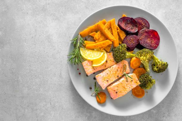 salmón frito con verduras. filete de pescado a la plancha con papas fritas en plato, vista superior. - dieta paleolítica fotografías e imágenes de stock