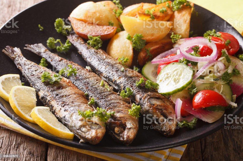 Fried sardines with potatoes and fresh vegetable salad close-up. horizontal stock photo