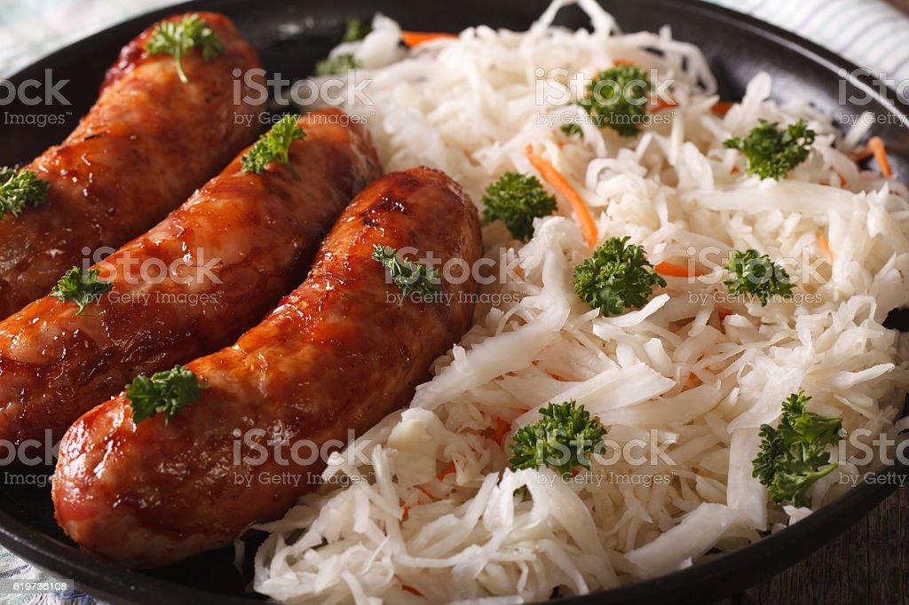 Fried sausage and sauerkraut on a plate macro. horizontal stock photo