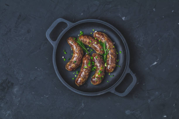 Fried sausage in a frying pan, with herbs and spices stock photo
