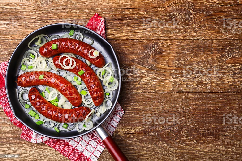 Fried sausages in a pan with onions. royalty-free stock photo