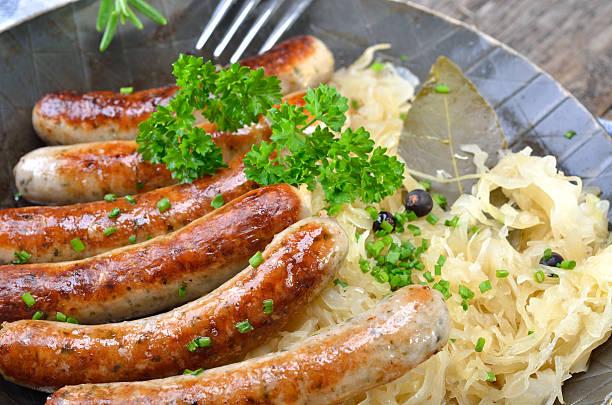 gebratener wurst mit sauerkraut - bratwurst mit sauerkraut stock-fotos und bilder