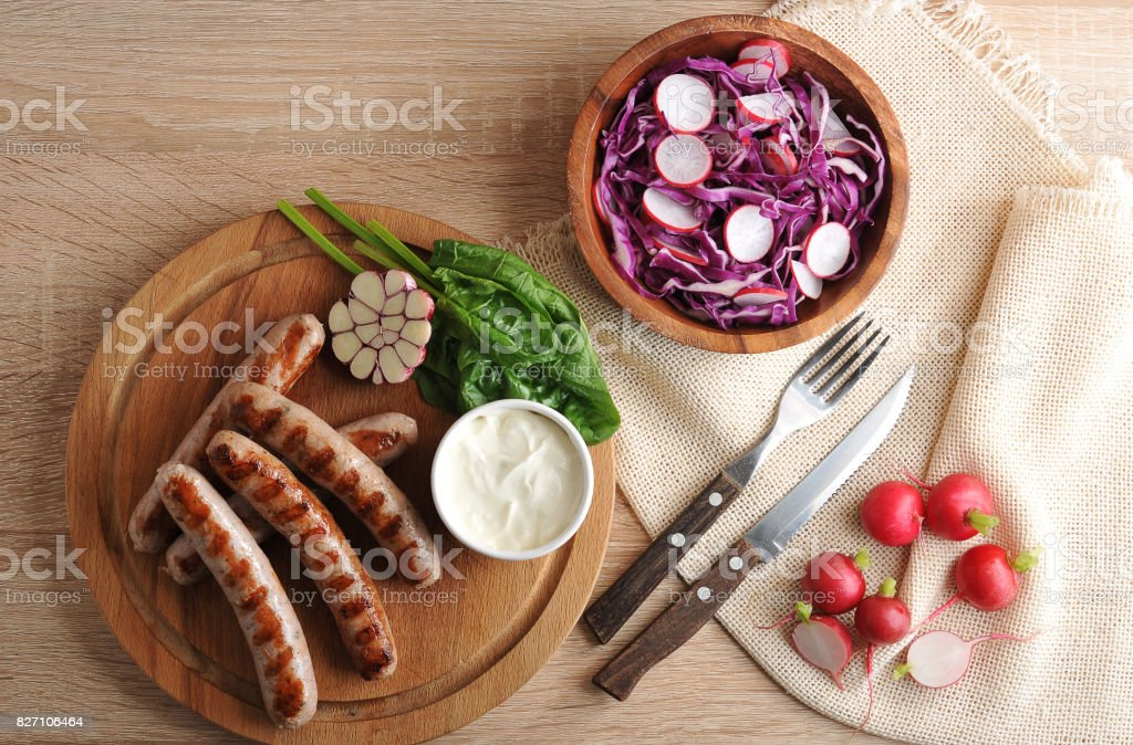 fried sausages on the grill with cream sauce and a salad of radish with red cabbage