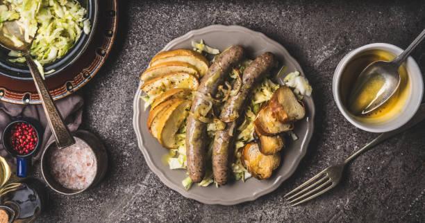 gebratene würstchen mit gebackenen äpfeln, zwiebeln und lauge brötchen toast serviert auf rustikalen tisch mit weißen krautsalat salat und senf-dip - bavaria porzellan stock-fotos und bilder