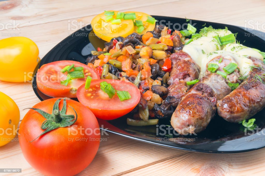 Fried sausages with vegetables on a kitchen table with tomatoes stock photo